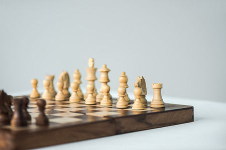 Partial view of chees board with chess pieces isolated on white