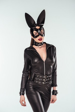 Seductive young woman in catsuit and mask with ears isolated on white Stock Photo