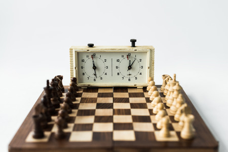 Chess board with figures set for new game and chess clock isolated on white