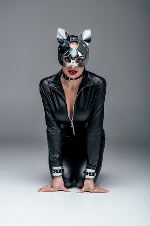Kinky woman in sexy costume and mask sitting in submissive position