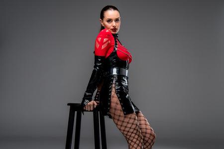 Attraktives heißes Mädchen, das sich auf Stuhl auf grauem Hintergrund stützt
