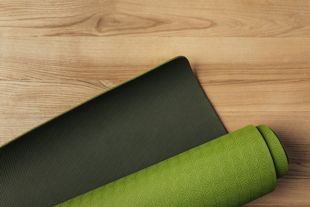 top view of green rolled yoga mat on wooden floor