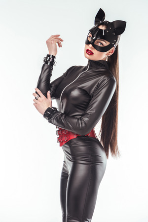 Seductive young woman in leather catsuit and mask isolated on white