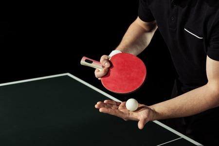 colpo ritagliato del giocatore di tennis con pallina da tennis e racchetta in mano isolato su nero Archivio Fotografico