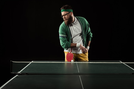 bearded tennis player leaning on racket on tennis table isolated on black Stock Photo - 111602648