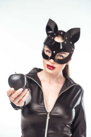 Black apple in hands of kinky woman in sexy costume isolated on white