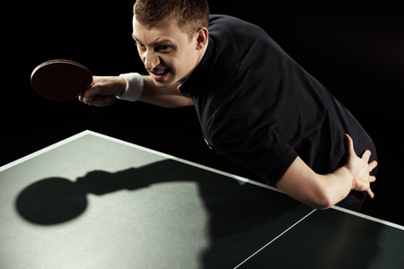 giocatore di tennis arrabbiato in uniforme che gioca a ping pong isolato su nero