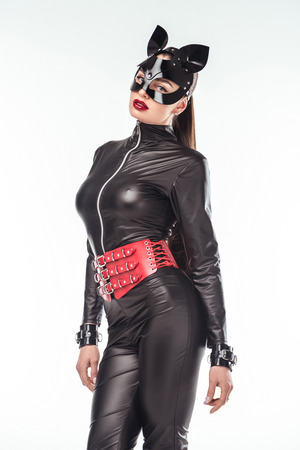 Attractive hot girl in leather costume and mask isolated on white