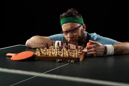 pensive bearded man looking at chess board on tennis table isolated on black 写真素材
