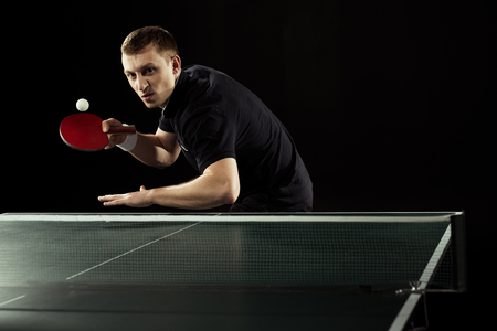 emotional tennis player in uniform playing table tennis isolated on black Banque d'images