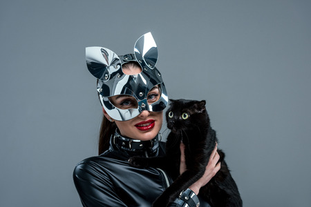 Seductive young woman in mask holding black cat isolated on grey