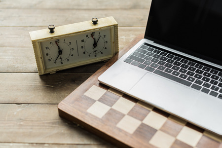 Chess clock, laptop and chess board on rustic wooden surface 写真素材
