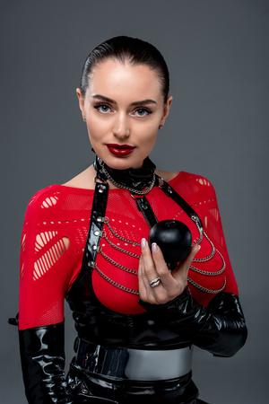 Jolie fille chaude tenant une pomme noire isolée sur fond gris Banque d'images