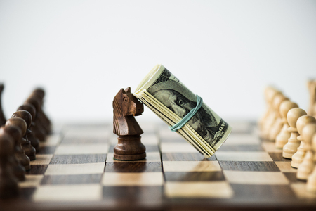 Close up view of chess board with cash and black knight isolated on white