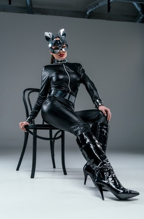 Seductive young woman in catsuit posing on chair on grey background Stock Photo - 111603522