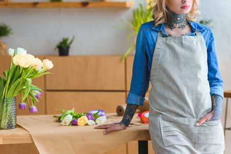 cropped shot of florist in apron leaning at table with beautiful tulip flowers Stock Photo - 111603542