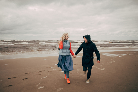 happy young couple holding hands and running on seashore in Riga
