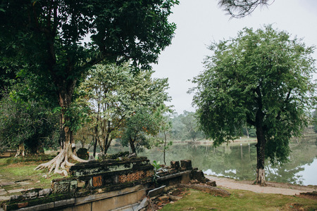 ruins of ancient architecture and green trees near calm pond in Hue, Vietnam