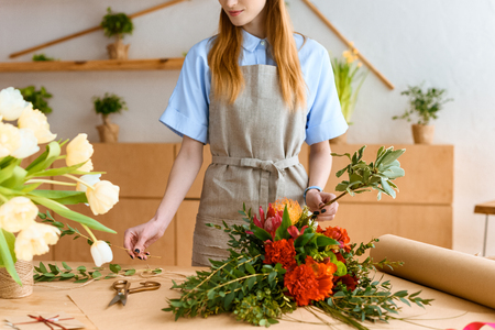 cropped shot of young florist in apron working with flowers