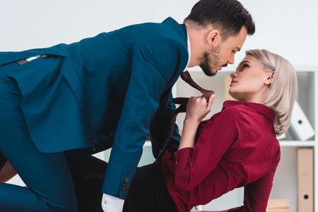 Seductora joven pareja de empresarios mirando el uno al otro en el lugar de trabajo