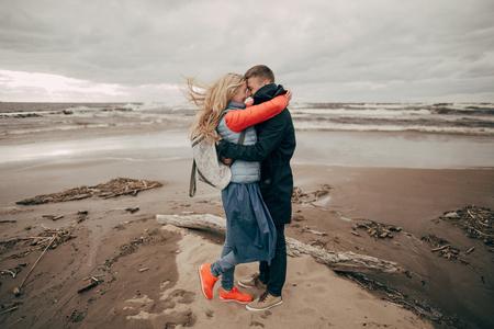 happy young couple hugging on seashore in Riga Stock Photo