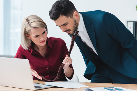businesswoman holding necktie of handsome businessman and showinglaptop at papers in office