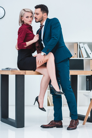 sexy young couple of business people flirting in office