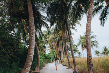 back view of girl walking between palm trees at Ukulhas island, Maldives
