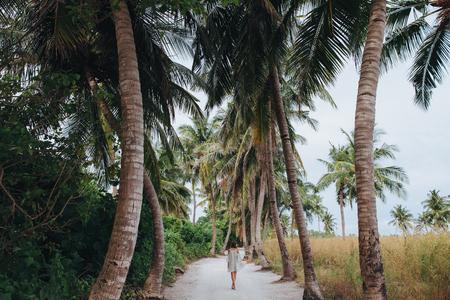 Vista posterior de la niña caminando entre palmeras en la isla de Ukulhas, Maldivas Foto de archivo