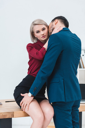 young couple of business people kissing and flirting at workplace