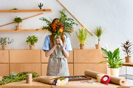 young florist in apron hiding face behind beautiful flower bouquet at workplace Imagens