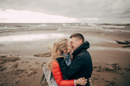 beautiful young couple kissing on sandy beach of Baltic sea