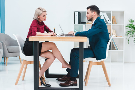 side view of young couple of business people looking at each other while working together and flirting under table in office Banque d'images