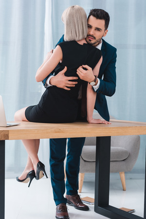 businessman and businesswoman hugging in at workplace