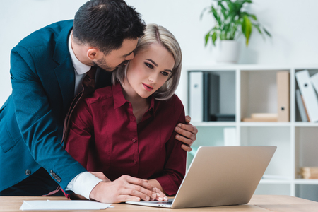 businessman flirting with beautiful female colleague using laptop in office
