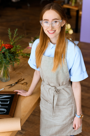 beautiful smiling young florist leaning at table with open sign