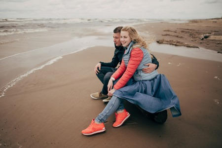 happy young couple sitting on log and looking at Baltic sea in Riga