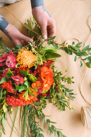 close-up partial view of woman arranging beautiful flowers into bouquet Stock Photo