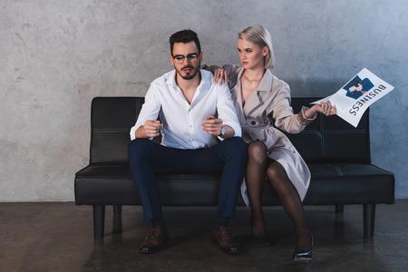 Mädchen in Mantel und Strümpfen, die Zeitung halten und mit einem gutaussehenden Geschäftsmann flirten Standard-Bild