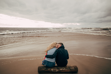 back view of young couple sitting on log and kissing near Baltic sea Foto de archivo - 111692472
