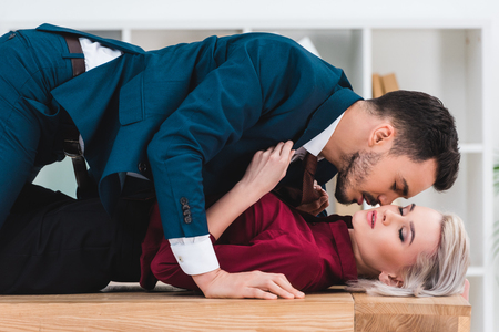 side view of sexy young couple kissing on table in office Banque d'images