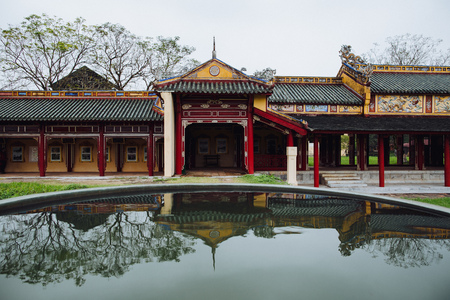 traditional oriental architecture with reflection in calm pond, Hue, Vietnam