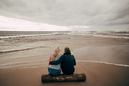 back view of young couple sitting on log and looking at beautiful wavy Baltic sea Stock Photo
