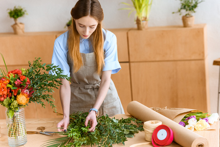 beautiful young florist in apron arranging green plants in flower shop Stok Fotoğraf - 111692122
