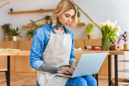 young florist in apron using laptop in flower shop