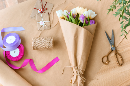 top view of beautiful bouquet of tulips, scissors, ribbons and envelopes with rope on craft paper