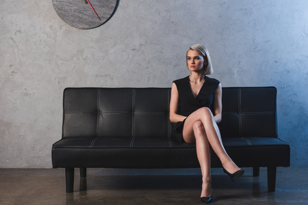 beautiful blonde girl in black dress and high heeled shoes sitting on couch and looking away