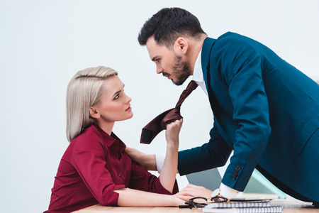 side view of young businesswoman holding necktie of handsome businessman in office Imagens