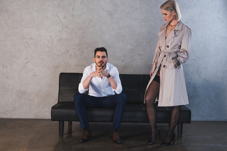 girl in coat and stockings flirting with handsome young businessman sitting on couch