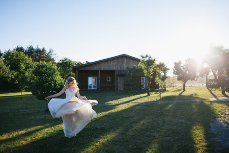 beautiful young bride in white wedding dress dancing on green lawn Banco de Imagens